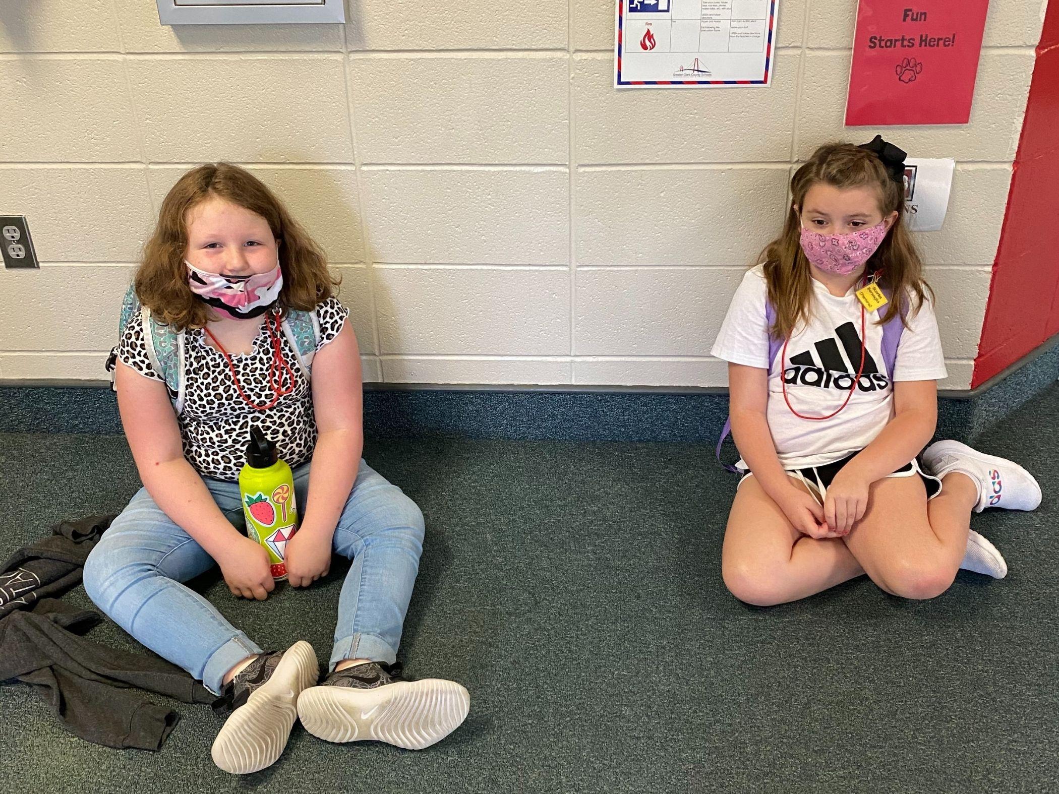 Two children wait in the hallway
