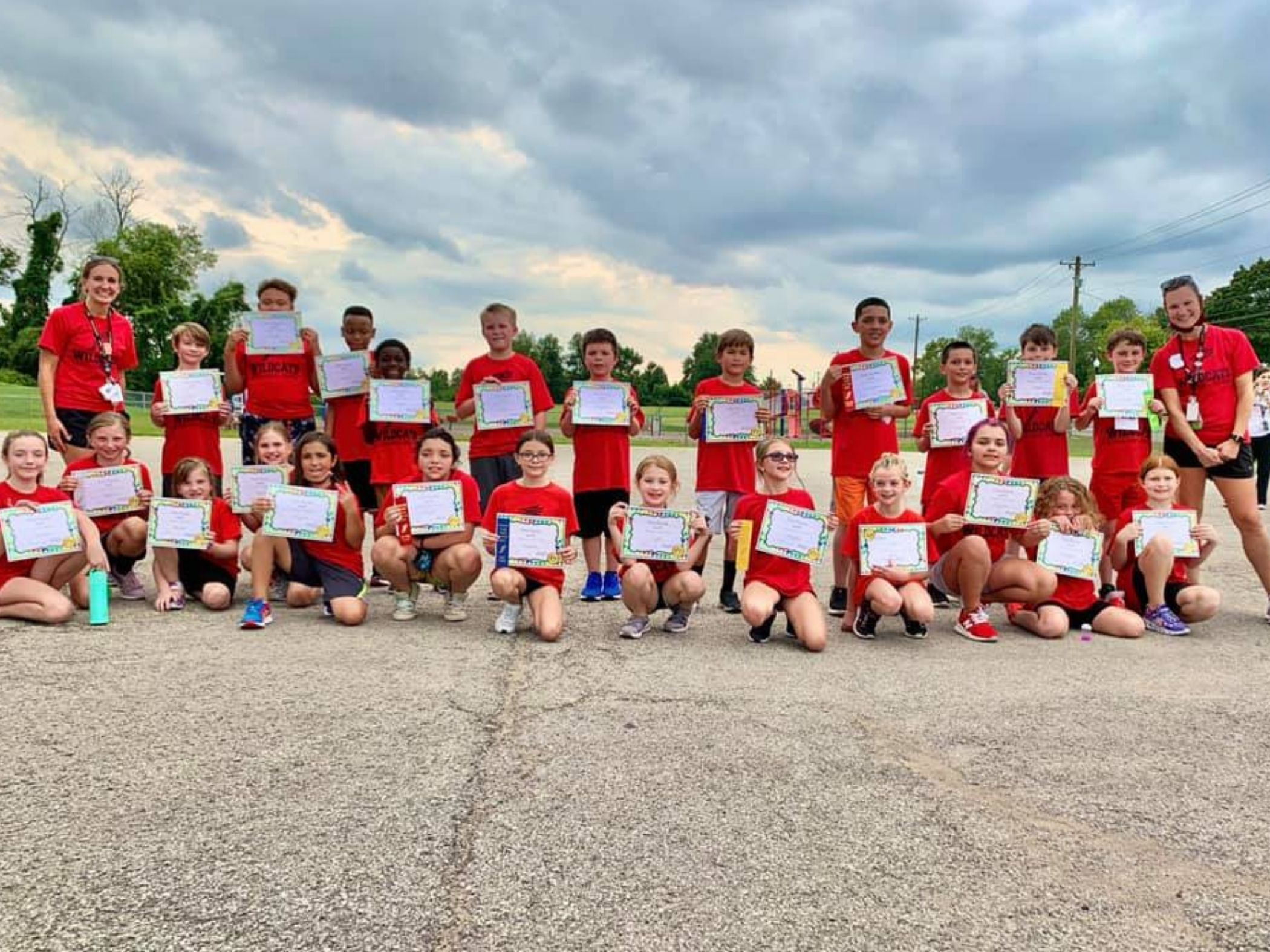 Students pose with certificates following cross country meet